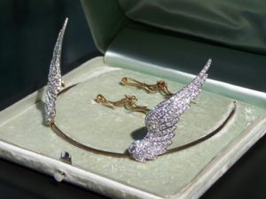 """Ida McKinley's diamond tiara was sold in 2014 to Rick Harrison on the History Channel's television show """"Pawn Stars."""" Harrison gave the Museum three months to raise $43,000 – the amount he paid – to buy it from him. Almost 400 donors from 22 states sent money to help the Museum meet its goal. The tiara is now on display in the McKinley Gallery. It was made by J. Dreicer & Son in New York City. It consists of approximately 200 diamonds, 100 on each wing. The wings are detachable and can be worn separately as matching brooches. Women would have worn them on their collar or lapel, or possibly on a fabric belt. There is a small screw mechanism on the back of each wing which allows it to be attached to the pin base or the plain gold tiara band."""